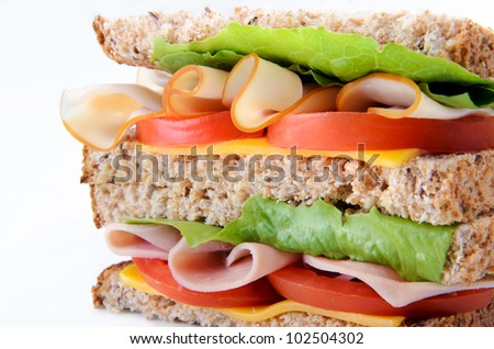 Close up healthy sandwich cross-section with ham and turkey with salad