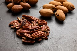 Close up heap of pecan on the black table. Heap unpeeled nuts on the background