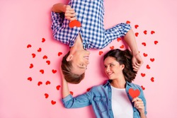 Close up high angle photo of pair in love he him his she her lady boy lying on floor  cuddle to each other with little red paper hearts wearing casual shirts outfit isolated on pale rose background