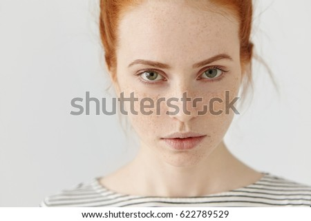 Close up highly-detailed picture of beautiful charming young female with perfect freckled skin, ginger hair and green eyes resting indoors, dressed in sailor t-shirt. Teenage girl posing in studio - Shutterstock ID 622789529
