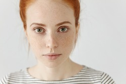 Close up highly-detailed portrait of amazing charming young European woman with ginger hair and perfect healthy freckled skin, wearing striped t-shirt, looking at camera with pretty cute smile