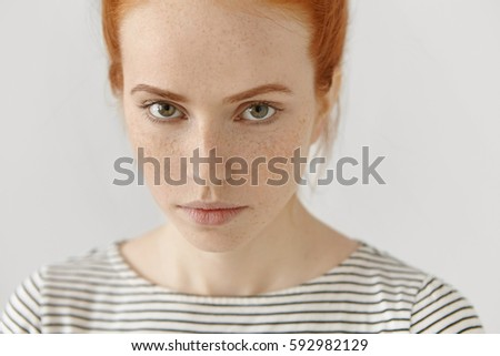 Close-up highly-detailed portrait of amazing young redhead female model with green eyes and clean healthy skin with lots of freckles dressed in striped t-shirt, looking at camera with subtle smile - Shutterstock ID 592982129