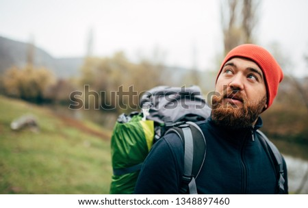 Close up horizontal outdoor portrait of hiker young male hiking in mountains with travel backpack. Traveler man with beard trekking and mountaineering. Travel, people, healthy lifestyle concept