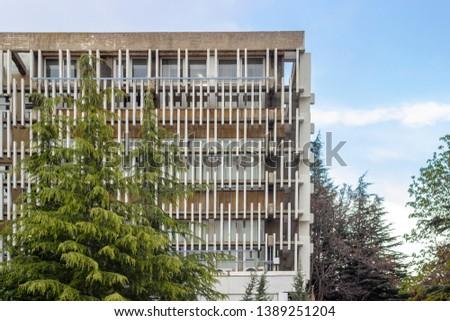 Close-up horizontal shoot of horizontal modern design concrete shading elements with trees #1389251204