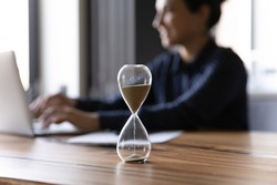 Close up hourglass measuring time, standing on wooden office table, Indian businesswoman working on background, efficiency, deadline and time management concept, busy employee using laptop