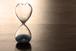 Close up hourglass on wooden floor for time concept, sepia effect used