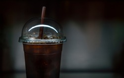 Close up Iced Americano with brown colour straw on dark tone background.  Iced Americano in plastic take away glass, blank space for logo brand on front of plastic take away glass.