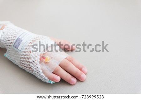 Close Up Illness of little asian toddler girl wearing saline intravenous (IV) on hand.
