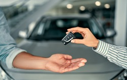 Close-up image a man buys a car and receives keys from the seller.
