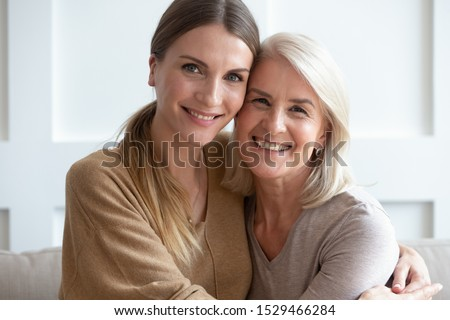 Close up image aged mother adult daughter sitting on couch indoors smiling looking posing for camera hugging feels happy spend time together, concept of love relative people, multi-generational family