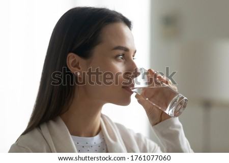 Close up image beautiful woman holding glass drinking still clean water looking in distance. Concept of healthy lifestyle, aqua boosts skin health and beauty, dehydration prevention natural treatment