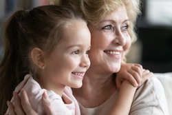Close up image caring elderly grandmother and small granddaughter embracing looking aside happy multi-generational family relatives people portrait, understanding strong attachment best friend concept