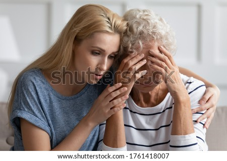 Close up image caring young grown up daughter soothes hugs mature mother showing care and support empathy, provides moral psychological help in difficult period of life, bad news about disease concept