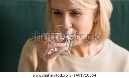Close up image elderly attractive woman holding in hand glass with clear aqua drinking still or mineral water, aged sixty years female feels thirsty, body skin and health care healthy habit lifestyle