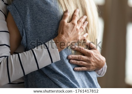 Close up image elderly woman hugs younger relative girl. Grown up adult daughter or granddaughter enjoy moment cuddle to old mom or aged granny. Family bond, together in trouble and happiness concept Foto stock ©