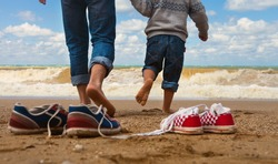 Close up image father and son legs walk at the seaside