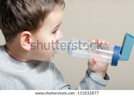 Close-up image little boy using inhaler for asthma.