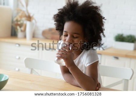 Close up image little mixed-race girl sitting at table in kitchen holding glass enjoy still or mineral water reduces thirst drinks clear aqua, healthy beverage, natural hydration body balance concept