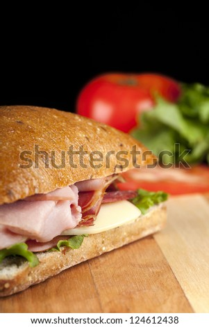 Close-up image of a bacon sandwich on a wooden table with a blurred tomato on the background