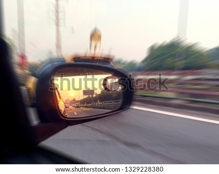 Close up image of a car side mirror with a view of sunrise. Motion blur motion background. Selective focus, shallow depth of field.  #1329228380