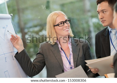Close-up image of a ceo pointing at the data on the board while talking with her colleagues on the foreground
