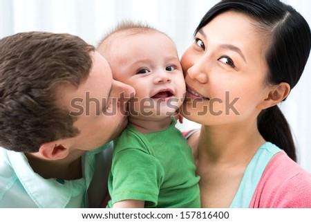 Close-up image of a cheerful family with a funny little boy on the foreground