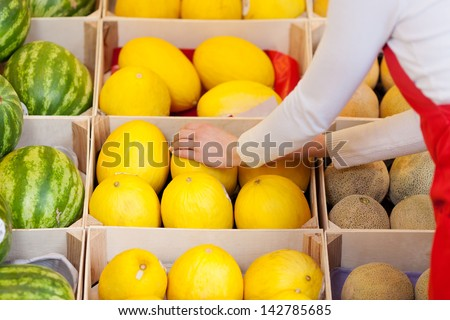 Close-up image of a female worker stacking melons in the supermarket.