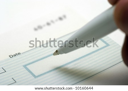 Close up image of a generic blank check being signed
