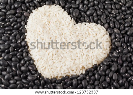 Close-up image of a heart shape rice grains isolated on the dark beans