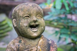 Close up image of a laughing child buddha statue carved in weathered stone, in a temple garden in Thailand
