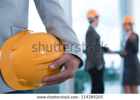 Close-up image of a male worker holding a hardhat, his colleagues can be seen in the background