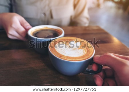 Close up image of a man and a woman clinking blue coffee mugs on wooden table in cafe