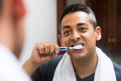 Close-up image of a man brushing the teeth in the apartment