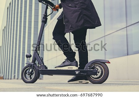 Close up image of a man on an electric scooter.