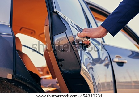 Close up image of a man opens car's door.
