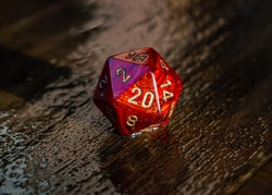 Close-up image of a marbled red 20 sided die on a wet wooden surface outside in the sunlight