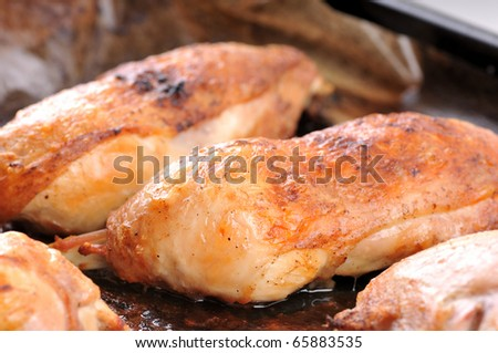 Close-up image of a roasted chicken leg on tray