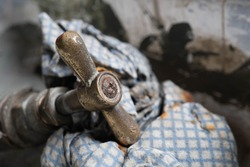 Close up image of a rusted antique brass tap with patina sat on an old blue and white cloth
