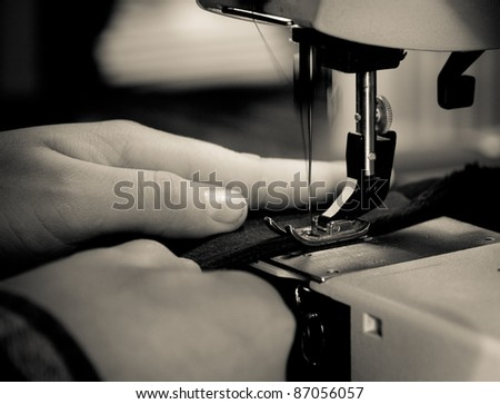 Close up image of a sew machine in use. Retro style with vignette
