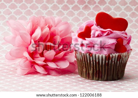 Close-up image of a strawberry cupcake with heart shapes and a pink flower.