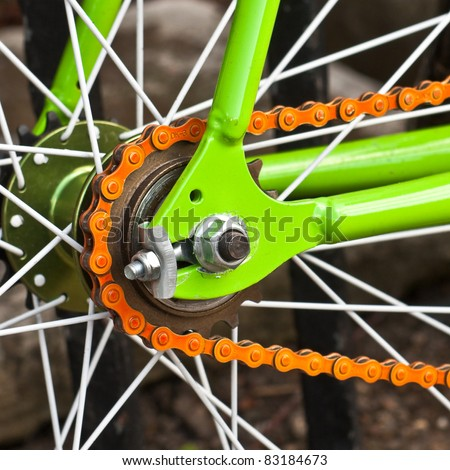 Close up image of a vibrant bicycle wheel with an orange chain