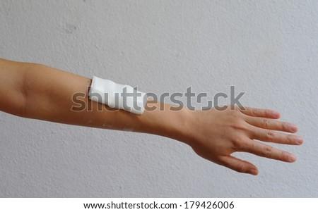 Close-up image of a white bandage wrapped on injured arm.