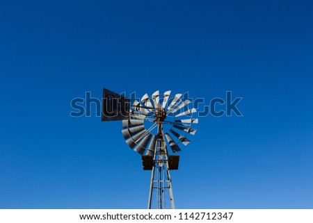 Close up image of a windpump / windmill /windpomp against a bright blue sky in the karoo of south africa