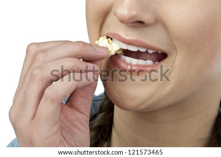 Close-up image of a woman eating popcorn over the white surface