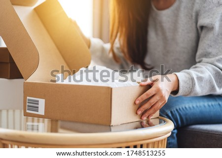 Close up image of a woman receiving and opening a postal parcel box at home for delivery and online shopping concept Foto stock ©