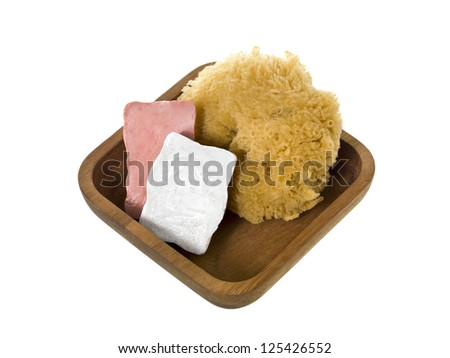 Close-up image of a wooden container with bar soap and loofah isolated on a white background