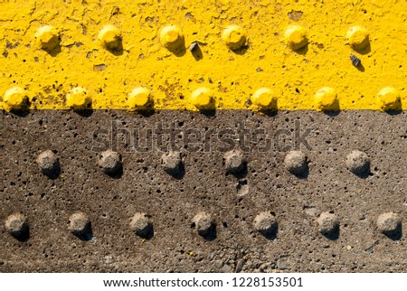 "Close up image of a yellow ""Keep Behind This Line"" warning from an Irish train station. #1228153501"