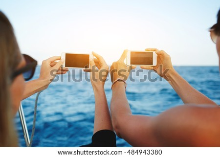 Close up image of a young man and woman travelers are holding mobile phone with blank copy space screen for your advertising text message or promotional content during their rest near sea in summer #484943380