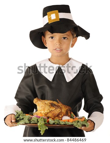 Close-up image of an adorable preschool boy in Pilgrim clothes holding a wooden platter with roast foul surrounded by colorful vegetables.  On a white background.