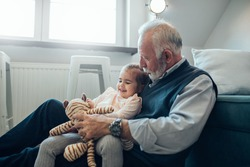 Close-up image of an elderly man holding his granddaughter